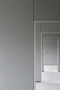 Empty corridor leading towards closed door in officeの写真素材 [FYI04323295]