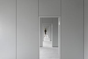 View through corridor of businesswoman walking in officeの写真素材 [FYI04323307]