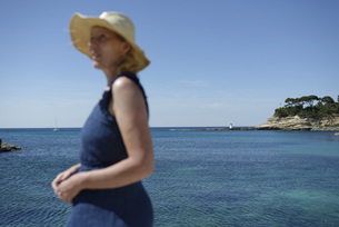 Side view of woman standing by seascape against clear skyの写真素材 [FYI04323309]