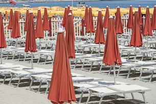 Closed red parasols and lounge chairs on beachの写真素材 [FYI04323315]