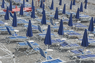 Closed blue parasols and lounge chairs on beachの写真素材 [FYI04323320]