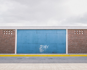 Text on blue wall against cloudy skyの写真素材 [FYI04323330]