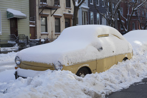 Snow covered car on street in cityの写真素材 [FYI04323333]