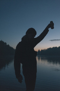 Silhouette of woman holding drink can by lake during sunsetの写真素材 [FYI04323355]