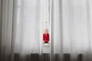 Doll sitting on windowsill behind curtainsの写真素材 [FYI04323367]