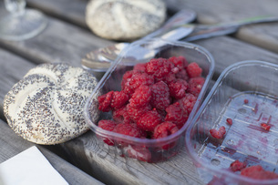 Raspberries in container by bread roll on tableの写真素材 [FYI04323368]