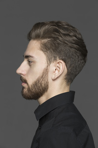 Side view of young man looking away against gray backgroundの写真素材 [FYI04323377]