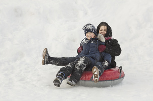 Portrait of happy grandmother and grandson sitting on inflatable ring in snowの写真素材 [FYI04323378]