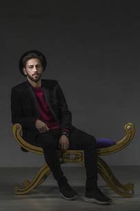 Portrait of confident man sitting on old-fashioned ottoman against gray backgroundの写真素材 [FYI04323381]