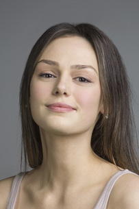 Portrait of beautiful young woman against gray backgroundの写真素材 [FYI04323383]