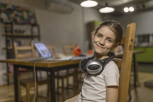 Portrait of smiling girl wearing headphones around neck while sitting on wooden chair at homeの写真素材 [FYI04323384]