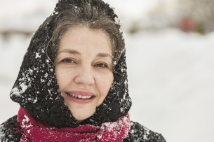 Portrait of smiling senior woman in winter wear covered with snowの写真素材 [FYI04323385]