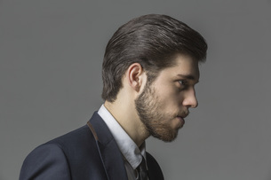 Side view of thoughtful businessman against gray backgroundの写真素材 [FYI04323387]