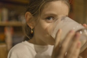Close-up portrait of cute girl drinking milk at homeの写真素材 [FYI04323388]