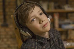 Thoughtful boy listening music through headphones at homeの写真素材 [FYI04323391]