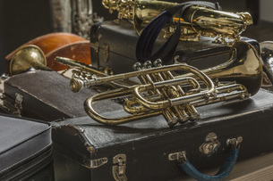 High angle view of brass musical instruments and trunks on floorの写真素材 [FYI04323396]