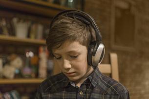 Boy listening music through headphones at homeの写真素材 [FYI04323397]
