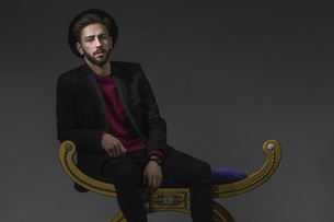 Portrait of confident man sitting on old-fashioned ottoman over gray backgroundの写真素材 [FYI04323409]