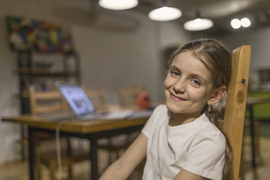 Portrait of smiling girl sitting on wooden chair at homeの写真素材 [FYI04323410]