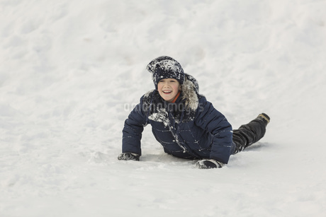 Cheerful boy looking away while lying in snowの写真素材 [FYI04323411]