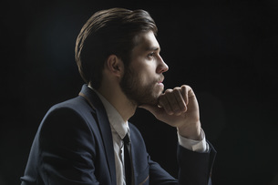 Side view of thoughtful businessman with hand on chin against black backgroundの写真素材 [FYI04323412]