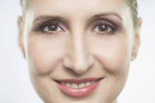 Close-up portrait of smiling mid adult woman against white backgroundの写真素材 [FYI04323415]