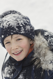 Portrait of happy boy in winter wear covered with snowの写真素材 [FYI04323418]