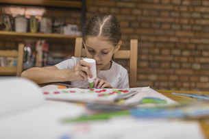 Girl applying glue on paper while making craft product at homeの写真素材 [FYI04323421]