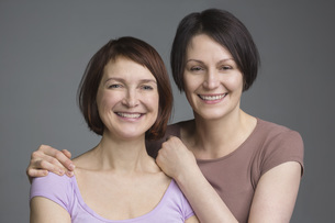 Portrait of happy mature female friends against gray backgroundの写真素材 [FYI04323423]