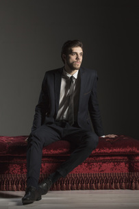 Full length thoughtful businessman sitting on ottoman against gray backgroundの写真素材 [FYI04323424]