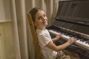 Side view portrait of cute girl playing piano at homeの写真素材 [FYI04323425]