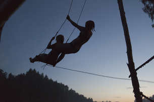 Low angle view of silhouette women swinging against clear sky during sunsetの写真素材 [FYI04323431]