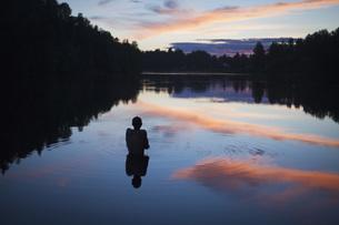 Rear view of shirtless boy in lake during sunsetの写真素材 [FYI04323440]