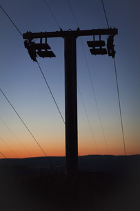 Low angle view of silhouette electricity pylon on field against sky during sunsetの写真素材 [FYI04323446]