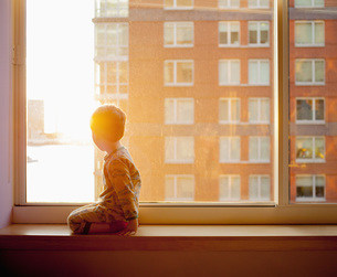 Side view of boy looking out while kneeling on window sill at homeの写真素材 [FYI04323451]