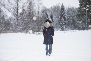 Full length portrait of mid adult woman standing on snow covered fieldの写真素材 [FYI04323455]