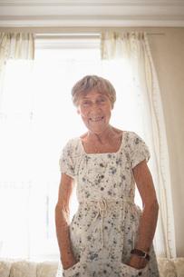Portrait of happy senior woman sanding at brightly lit homeの写真素材 [FYI04323456]