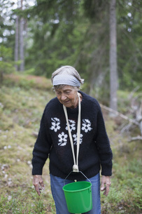 Senior woman carrying bucket in neck while walking on hillの写真素材 [FYI04323459]