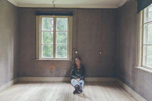 Portrait of confident woman sitting on hardwood floor at homeの写真素材 [FYI04323461]