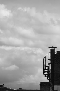 Low angle view of stairwell on building against cloudy skyの写真素材 [FYI04323464]