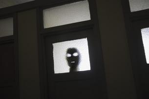 Mask seen through window of doorの写真素材 [FYI04323465]