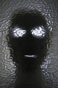 Close-up of mask seen through frosted glassの写真素材 [FYI04323479]
