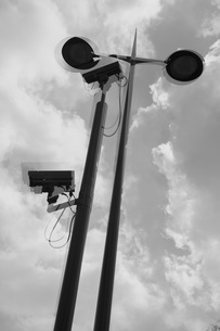 Multi-layered image of security cameras and street lights against cloudy skyの写真素材 [FYI04323481]