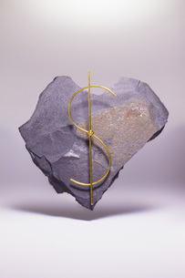 Dollar sign made of metallic wire on heart shape stone against white backgroundの写真素材 [FYI04323484]