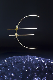 Euro symbol made of metallic wire levitating over shiny sand against black backgroundの写真素材 [FYI04323485]