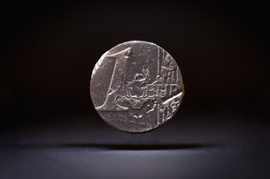 Close-up of damaged one euro coin levitating against black backgroundの写真素材 [FYI04323486]