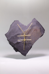 Yen sign made of metallic wire on heart shape stone against white backgroundの写真素材 [FYI04323490]