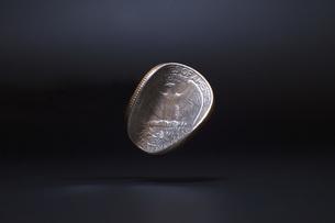 Close-up of damaged Washington quarter dollar levitating against black backgroundの写真素材 [FYI04323491]