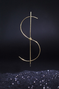 Dollar sign made of metallic wire levitating over shiny sand against black backgroundの写真素材 [FYI04323492]