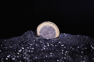 Close-up of one Euro coin in shiny sand against black backgroundの写真素材 [FYI04323494]